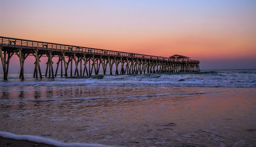 Myrtle Beach State Park pier jutting into the Atlantic Ocean with a sunset